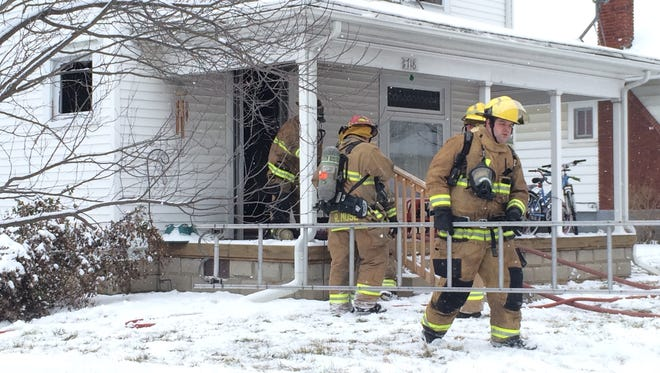 Richmond Fire Department personnel move equipment as the clean up the scene at a house fire on South West A Street.