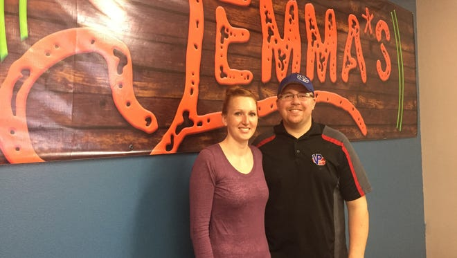Brittney and Justin Paiser stand in front of a newly hung sign inside of Jemma's Cafe.