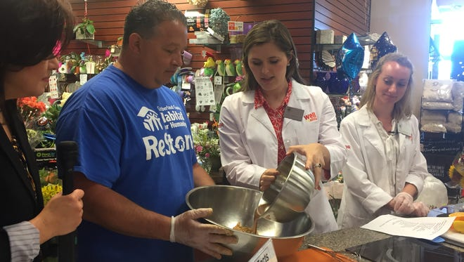 Bill Gonzalez, Cumberland County Habitat for Humanity executive director, works with Bottino ShopRite dietitians Kelsey DiVirgilio (center) and Diana Fiorentino (left) to convert his root beer chicken wings recipe recipe into a more healthy version.