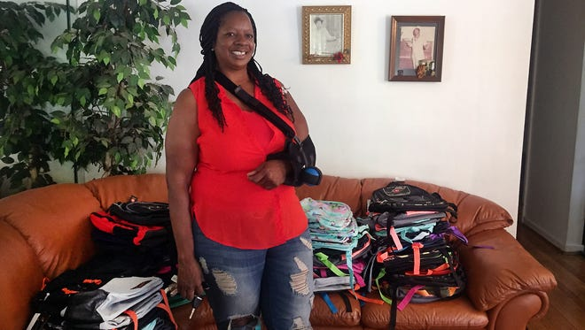 Anita Martin, 57, stands in her home on Detroit's east side on Sunday, August 27, 2017. Martin is surrounded by backpacks she gathered this year to donate to neighborhood kids before the new school year.