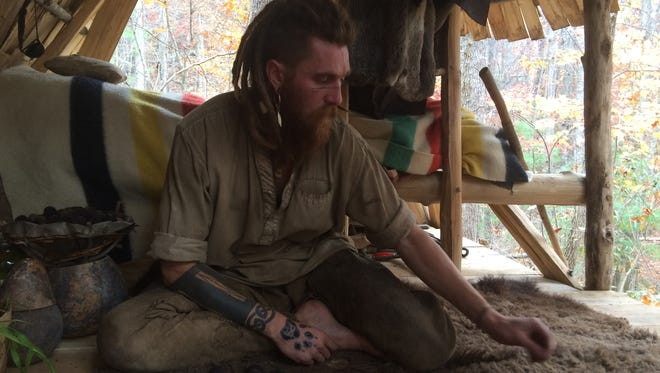 Thorn sits in his handmade home. He is a rewilder living in the woods of the Blue Ridge Mountains.