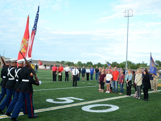 A Marine Corps Color Guard approaches the family of