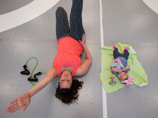 Melissa Alvarado of Magnolia works out with her daughter Cecilia (4 months) by her side during the MOMentum fitness Delaware fitness class at Delaware Combat Sports in Dover.