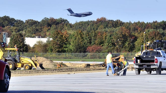 A heavy C-17 climbs out slowly after taking off in the background from runway 32 at Dover Air Force base in October 2015.