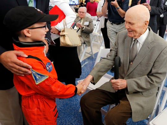 Former U.S. Sen. John Glenn, right, shakes hands with eight-year-old Josh Schick before the start of a celebration for the renaming of Port Columbus International Airport to John Glenn Columbus International Airport Tuesday, June 28, 2016, in Columbus, Ohio. Senate Bill 159, which changes the name of the airport, goes into effect in September.
