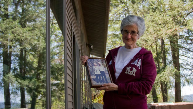 """In this June 1, 2017 photo, Marcia Sheffels, 72, holds a photo of her parents, who bought land on Whitefish Lake, in Whitefish, Mont., """"when it was cheaper ... than a lot downtown.""""  (Jayme Fraser/The Missoulian via AP)"""
