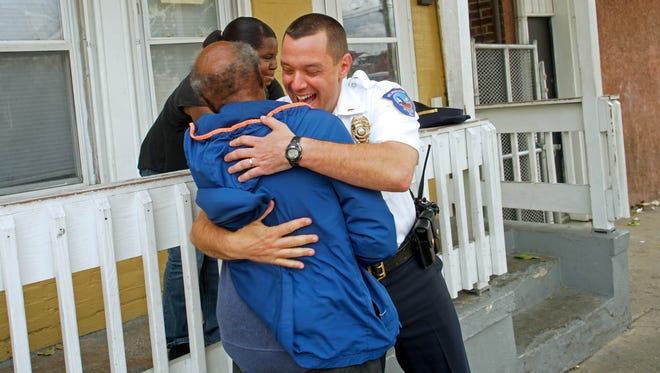Wilmington police officer Lt. Dan Selekman gives a hug to man who knew in West Center City while visiting residents.