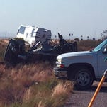 The scene of a bus crash is surveyed Sunday, July 24, 2016, on a highway in northwestern Arizona, about 30 miles north of Kingman. A Dallas Cowboys bus collided with another vehicle and authorities say at least one person was killed. Team spokesman Rich Dalrymple confirmed a Cowboys bus was one of two vehicles involved in the crash Sunday on U.S. 93.