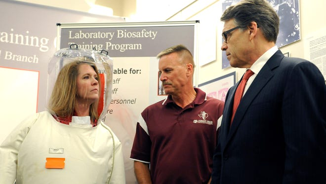 Texas Gov. Rick Perry, right, talks with a lab manager Terry Juelich, wearing a biohazard suit, and Curtis Klages at the Galveston National Lab Tuesday, Oct. 7, 2014, in Galveston, Texas. The Biosafety Level 4 lab conducts research on Ebola and other infectious diseases. Perry has created a 17-member task force to ensure Texas properly responds to infectious diseases like Ebola. (AP Photo/Pat Sullivan)