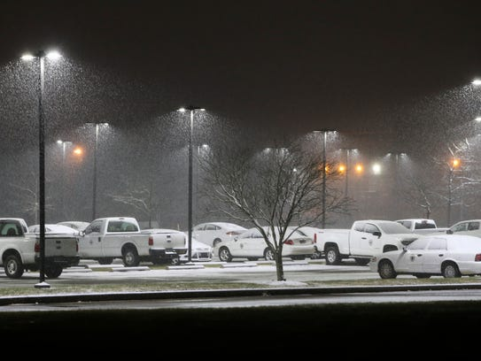 County vehicles are coated in snow at the New Castle