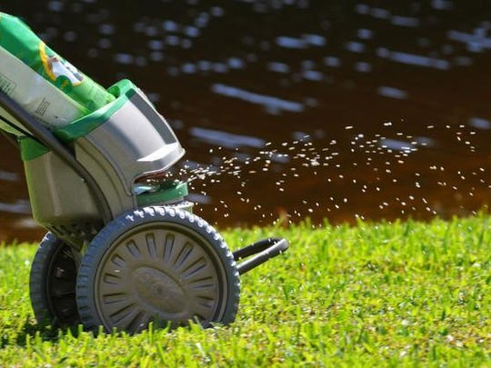 Mark Slavens, Ph.D., Lead, Regional Science & Technology with The Scott's Company, demonstrates the spreading of lawn fertilizer