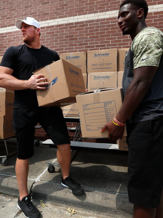 Houston Texans defensive end J.J. Watt, left, and running back Alfed Blue pick up boxes of relief supplies to distribute to people impacted by Hurricane Harvey on Sunday, Sept. 3, 2017, in Houston. Watt's Hurricane Harvey Relief Fund has raised millions of dollars to help those affected by the storm. (Brett Coomer/Houston Chronicle via AP, Pool)