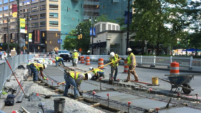 Workers lay cement for the M-1 rail on the southbound side of Woodward at Campus Martius in downtown Detroit on Wednesday, Aug. 5, 2015.