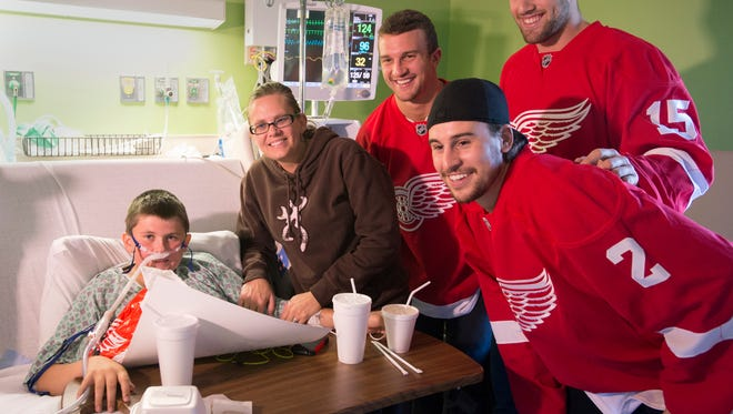 Detroit Red Wings NHL hockey players, third from left, Luke Glendening, Brendan Smith, left, and Riley Sheahan pose for a photo with Dennis Lapczynski III, 14, and his mother Andrea Holbrook on the pediatric floor of Covenant HealthCare in Saginaw, Mich., Wednesday, Sept. 17, 2014. Five members of the Red Wings, Luke Glendening, Brendan Smith, Riley Sheahan, Gustav Nyquist and Joakim Andersson are touring Michigan on a preseason caravan. (AP Photo/The Saginaw News, Jeff Schrier) ALL LOCAL TELEVISION OUT; LOCAL TELEVISION INTERNET OUT
