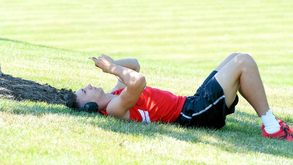 Riverheads' Michal Sagula relaxes in the shade of a lone tree as he waits to compete in the boys' shot put during the first day of the VHSL 2A state track and field championships in Radford on Friday, June 6, 2014.