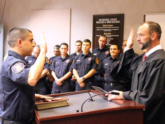 An Alamogordo firefighter is sworn into office by Judge