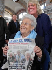 "Henriette Hanotte, code name ""Monique,"" holds a French newspaper with the story of her celebration on the front page. 'Monique' is 95, and was being given an honorary citizenship to the Bachy, France, community. The path she took with evaders was also being formally inaugurated as 'In Monique's Footsteps.' The path ran from Monique's hometown of Rumes, Belgium, to Bachy, France (neighboring towns)."