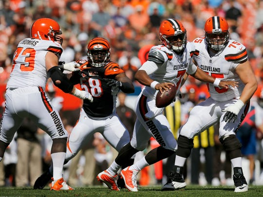 Cleveland Browns quarterback DeShone Kizer (7) scrambles away from a rushing Cincinnati Bengals linebacker Carl Lawson (58) in the first quarter of the NFL Week 4 game between the Cleveland Browns and the Cincinnati Bengals at FirstEnergy Stadium in downtown Cleveland on Sunday, Oct. 1, 2017. At halftime the Bengals led 21-0.