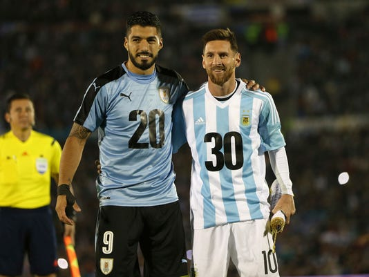 Argentina's Lionel Messi and Uruguay's Luis Suarez pose for pictures wearing the number 20 and 30 as the support the candidacy of Uruguay and Argentina for the 2030 World Cup before a 2018 World Cup qualifying soccer match in Montevideo, Uruguay, Thursday, Aug. 31, 2017.(AP Photo/Natacha Pisarenko)