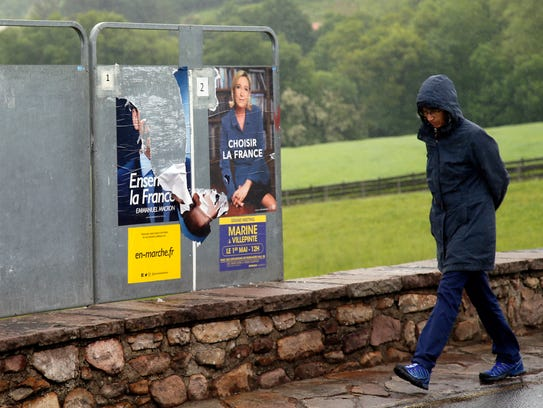 A woman walks past election posters of French centrist