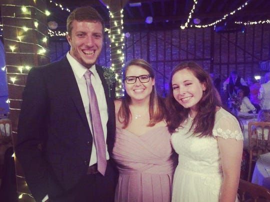 Girten poses for a photo with the bride and groom,