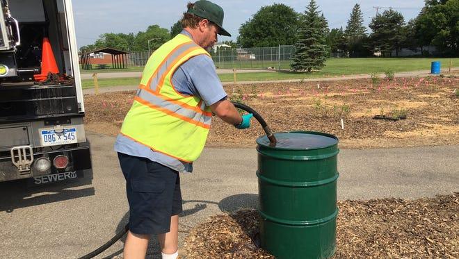 Westland employee Dave Evans fills water barrels so volunteers can tend the plants.