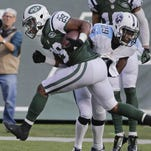 Jets running back Bilal Powell (29) runs past Titans' Perrish Cox (29) for a touchdown.
