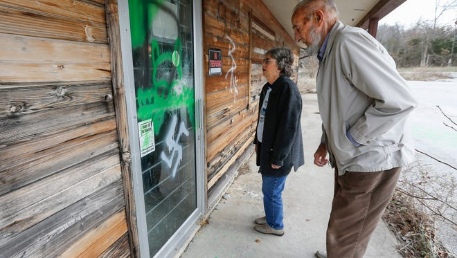 Glenn and Ann Edwards look at the graffiti that was spray painted on the front of the service station they own that is now vacant at the intersection of State Highway YY and MO-125 in Strafford. Glenn Edwards stated that Greene County contacted him and said he had 30 days to clean up the property. A group from the community has organized to help the couple clean up the property.