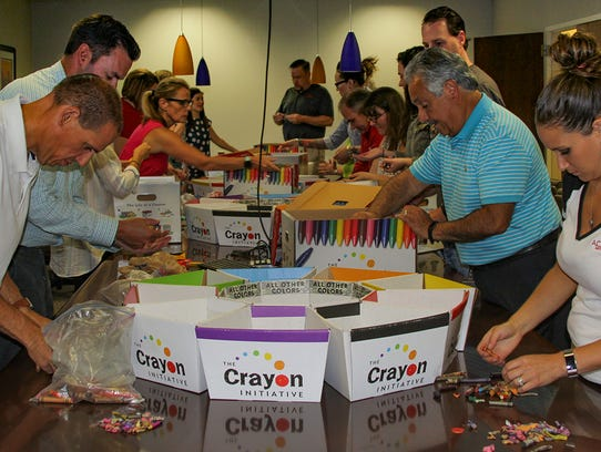 A.C. Moore team members sort through crayons at their