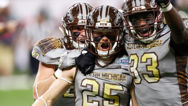 Trevor Sweeney (25) of the Western Michigan Broncos celebrates causing a fumble on a kick return with teammate Leo Ekwoge (33) while playing the Ohio Bobcats during the MAC Championship on December 2, 2016 at Ford Field in Detroit, Michigan.