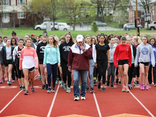 Verona High School Head Girl's Track and Field Coach, Gene Leporati, leads his team in a walk around the track in memory of Tom Fleming.  Leporati, of Wayne, knew Fleming for approximately 40 years. Thursday, April 20, 2017.
