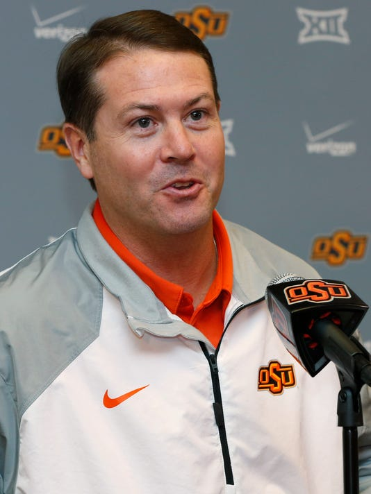 In this Monday, Oct. 20, 2014 photo, Oklahoma State head coach Travis Ford answers a question during an NCAA college basketball media day at Oklahoma State in Stillwater, Okla. Oklahoma State,  picked to finish near the bottom of the Big 12,  must replace stars Marcus Smart and Markel Brown. (AP Photo/Sue Ogrocki)