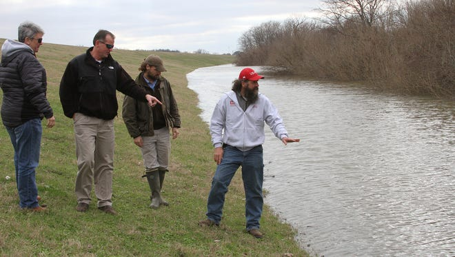 Members of the Deltq Joint Water Management District, Carol Davis, from left, Peter Nimrod, Chief Engineer Mississippi Levee Board, Taylor Bowling and Dan Kirkland look for potential problem areas along the river side of the levee Monday Jan. 4, 2016, in Greenville, Mississippi. The National Weather Service Monday lowered predicted crests along the Mississippi, with the high-water mark for Vidalia and cross-river neighbor Natchez, Mississippi dropping to 59 feet.