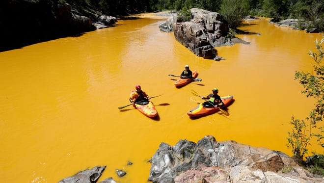 In this Aug. 6, 2015 photo, people kayak in the Animas River near Durango, Colo., in water colored from a mine waste spill.  The federal government and Colorado have made little progress in remedying damages from the 2015 release of millions of gallons of wastewater from a southern Colorado mine, New Mexico's top prosecutor charged in a pair of scathing letters sent to officials on Friday, May 20, 2016.