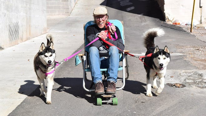 Georgie Cutright and his two Siberian Huskies, Sarah and Lobos, speed down a hill in Knoxville, Tenn., on Wednesday, Feb. 15, 2017. Cutright said he will attempt to travel from Knoxville to California, a more than 2,000-mile haul, on dog power alone.