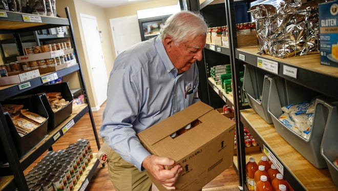 Nick Kestner, a volunteer of more than 10 years at the Carmel United Methodist Church Food Pantry, restocks juice on Monday, April 24, 2017.