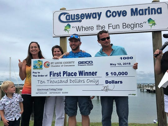 Stephanie Langel, Erin Chandler, Lyle Chandler and Phillip Langel all of St. Lucie County, hoist the winner's $10,000 check from Saturday's Fishing Frenzy fishing tournament.