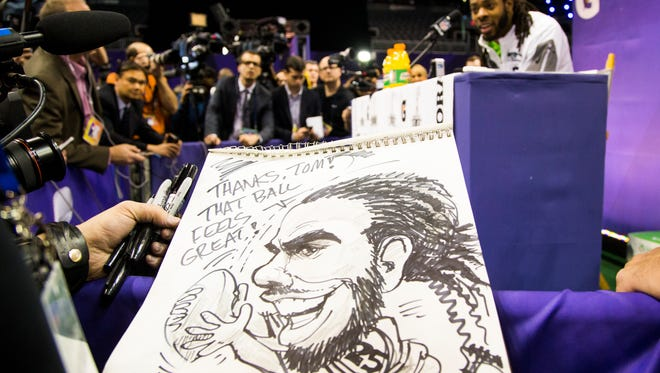The Arizona Republic editorial cartoonist Steve Benson draws a caricature of Seattle Seahawks CB Richard Sherman during Super Bowl Media Day at U.S. Airways Center in Phoenix January 27, 2015. The Seattle Seahawks will play the New England Patriots Sunday February 1 in Super Bowl XLIX in Glendale.