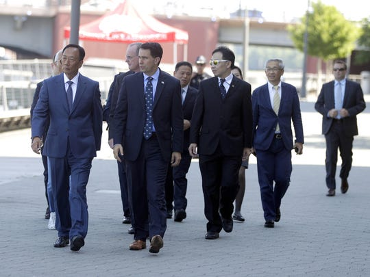 Foxconn CEO Terry Gau and Gov. Scott Walker walk down the CityDeck on June 29, 2018 before announcing Foxconn's new innovation center in downtown Green Bay. Sarah Kloepping/USA TODAY NETWORK-Wisconsin