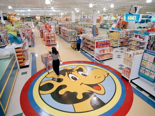 A woman pushes a shopping cart over a graphic of Toys R Us mascot Geoffrey the giraffe at the Toys R Us store in Raritan, N.J., on July 30, 1996.