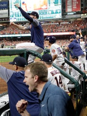 The Houston Astros dugout reacts after a home run hit