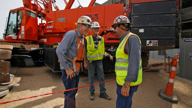 At right, Branch manager Vance Thurman talks with his employees Wednesday at a project site located at the San Juan Generating Station Waterflow.