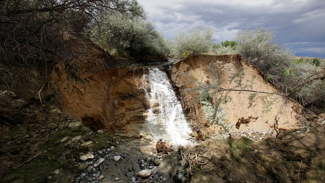 Irrigation water flows into an eroded section of the Bloomfield Irrigation Ditch off County Road 4655 in Blanco on Monday.