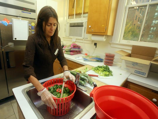 Kerry Rooney of Nyack rinses off lettuce for a salad as she and other volunteers prepare dinner for the needy at the Soup Angel's soup kitchen at the First Reformed Church in Nyack Nov. 11, 2017.