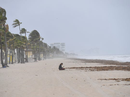 A woman looks checks her phone while sitting on the beach in Hollywood, Florida.