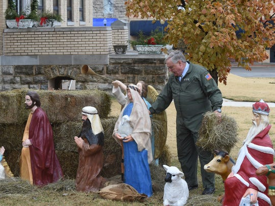 Rick Spencer spreads hay around a Nativity scene Thursday