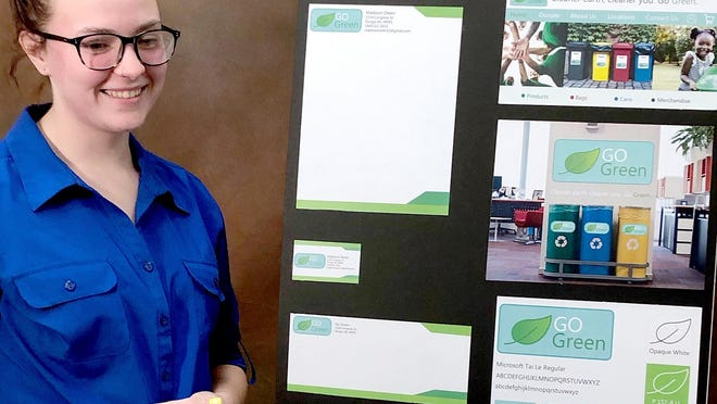 """Madison Owen of Sturgis with the display board featuring her recycling business, called """"Go Green."""""""