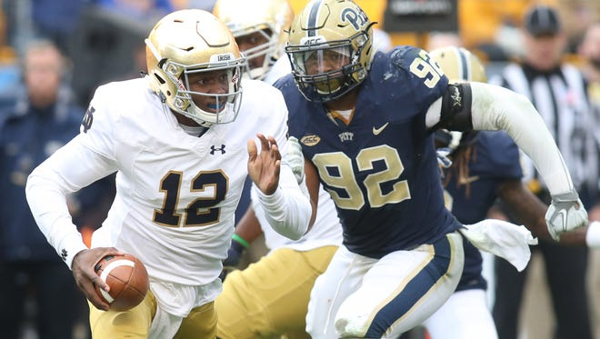 Nov 7, 2015; Pittsburgh, PA, USA; Notre Dame Fighting Irish quarterback Brandon Wimbush (12) scrambles with the ball as Pittsburgh Panthers defensive lineman Rori Blair (92) chases during the fourth quarter at Heinz Field. Notre Dame won 42-30. Mandatory Credit: Charles LeClaire-USA TODAY Sports