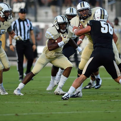 Team Gold sophomore running back Taj McGowan runs the ball down the field in the first half of the UCF spring football game classic. Team Gold beat Team Black, 21-10, on April 16.