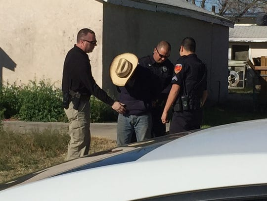 A man is arrested and searched at a home on 2nd Street
